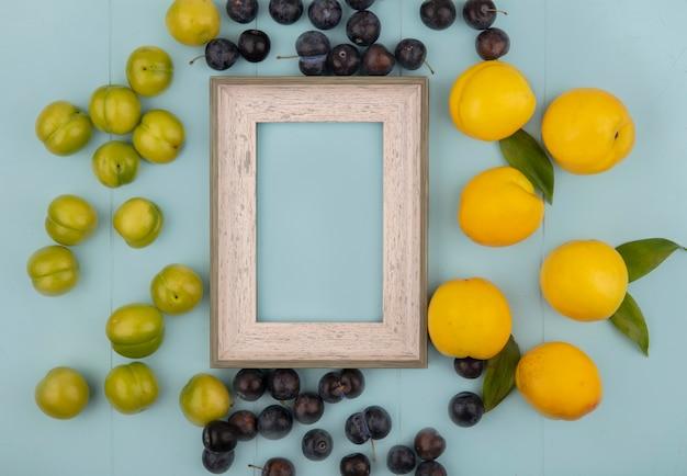 Вид сверху на свежие вкусные желтые персики с зелеными алычами с терном, изолированные на синем фоне с копией пространства