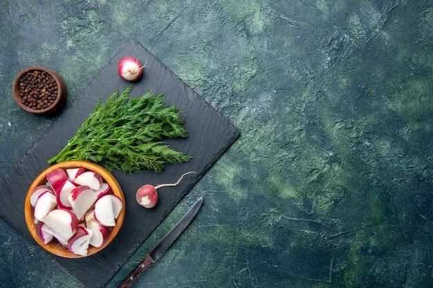 新鮮なディルの束と黒まな板の右側にあるみじん切り大根ナイフ全体の上面図緑と黒のミックスカラーの背景に空きスペースのあるペッパーナイフ