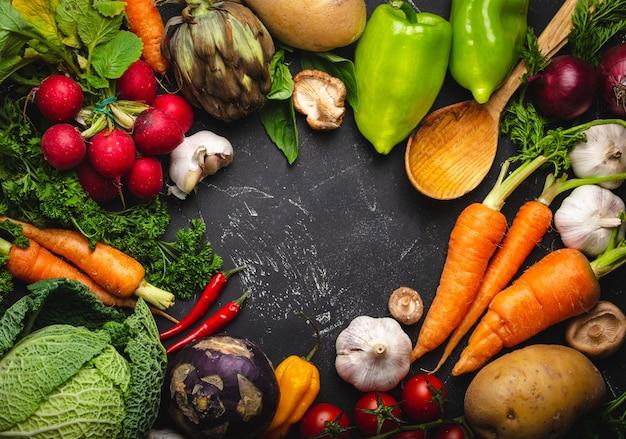 素朴な黒いコンクリートの背景に新鮮な農場の有機野菜、ハーブ、木のスプーンの上面図。秋の収穫、地元の市場、またはテキスト用のスペースを備えた清潔で健康的な食事のコンセプト