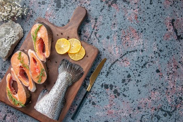 新鮮な魚の上面図レモンスライスグリーンペッパー木製まな板とナイフの青黒ミックスカラーテーブル