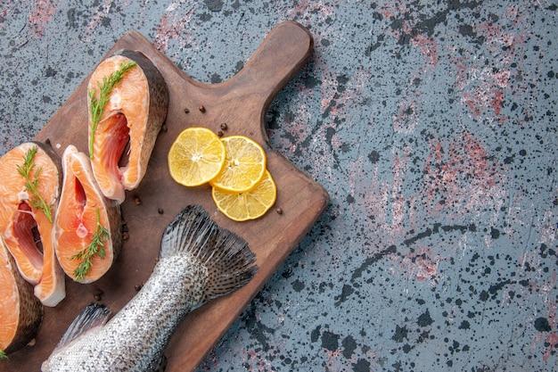 블루 블랙 믹스 색상 테이블에 나무 절단 보드에 신선한 물고기 레몬 슬라이스 녹색 후추의 상위 뷰