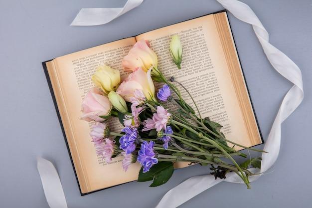 회색 배경에 고립 된 흰색 리본이 달린 신선한 꽃의 상위 뷰