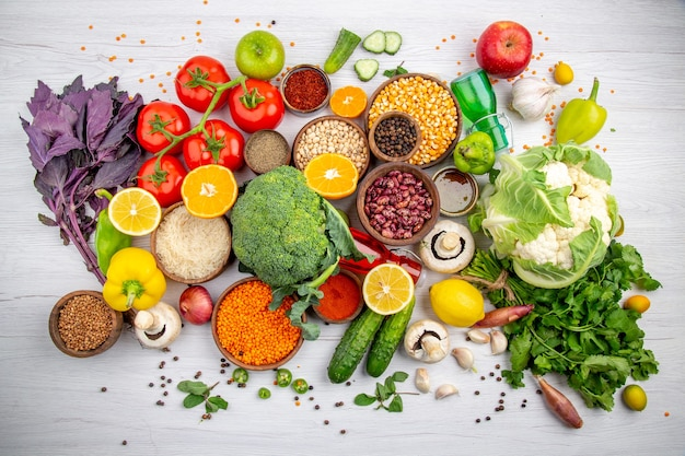 白いテーブルで調理するための生鮮食品とスパイス野菜の上面図