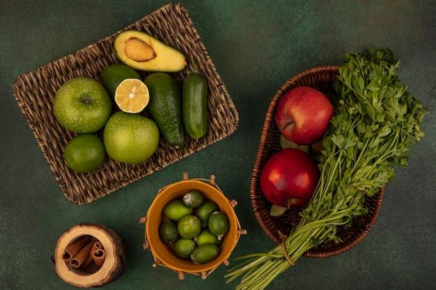 Вид сверху на свежие продукты, такие как зеленые яблоки, авокадо, огурец на плетеном подносе с фейхоа на ведре с красными яблоками и петрушкой на ведре на зеленой стене