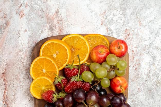 白い表面に新鮮な果物の組成オレンジブドウとイチゴの上面図