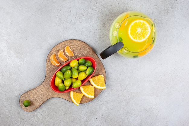 나무 보드에 오렌지와 귤 조각과 금귤의 더미와 함께 신선한 과일 레모네이드의 최고 볼 수 있습니다.