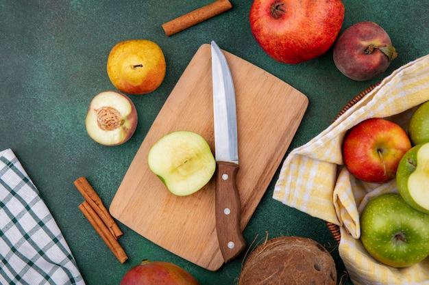 Вид сверху на свежие фрукты, такие как яблоко на деревянной кухонной доске, с ножом, персиком, гранатом, грушей и палочками корицы на зеленом