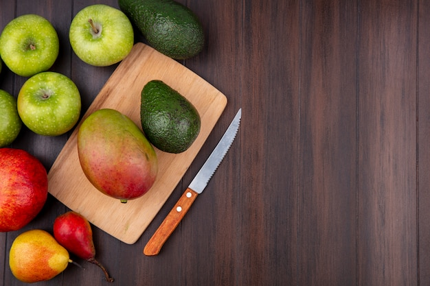 Вид сверху на свежие фрукты, такие как манго и авокадо, на деревянной кухонной доске с ножом и зелеными яблоками на дереве с копией пространства