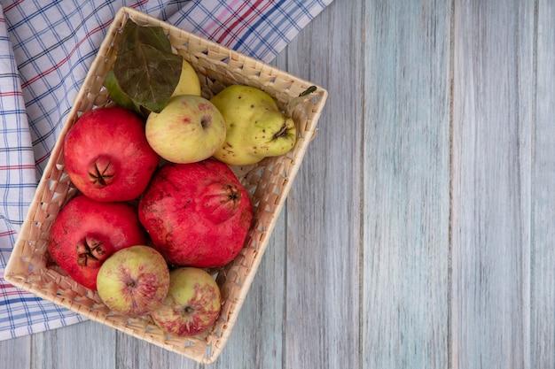 Вид сверху свежих фруктов, таких как гранаты, яблоки и айва, на ведре на клетчатой ткани на сером фоне с копией пространства