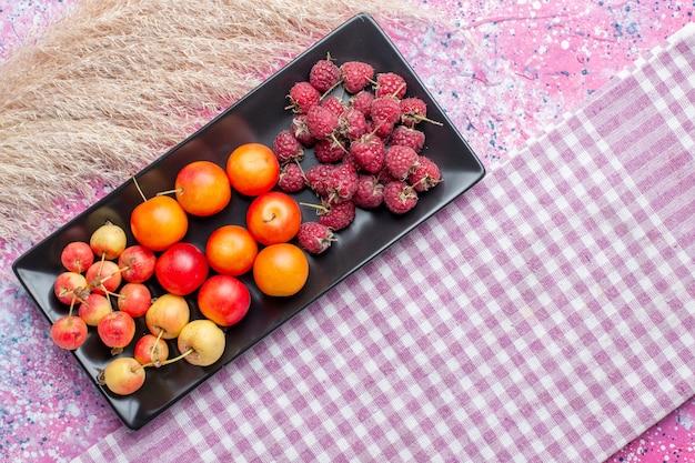 Вид сверху свежих фруктов малины и сливы внутри черной формы на розовой поверхности