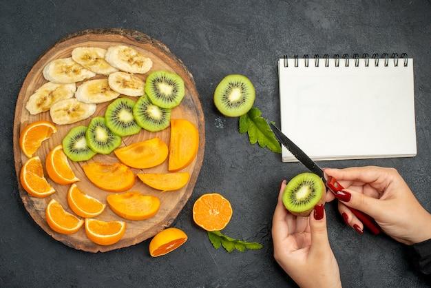 暗い背景のノートブックの横にあるキウイフルーツのスライスを手で刻む木製トレイにセットされた新鮮な果物の上面図