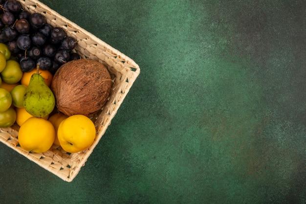 Вид сверху свежих фруктов, таких как кокосовая желтая персиково-зеленая груша на ведре на зеленом фоне с копией пространства
