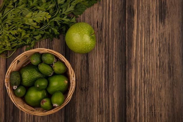 복사 공간이 나무 표면에 고립 된 사과와 파슬리 양동이에 feijoas와 라임과 같은 신선한 과일의 상위 뷰