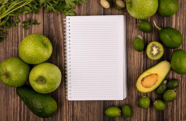 コピースペースのある木製の表面に分離された青リンゴライムフェイジョアアボカドやパセリなどの新鮮な果物の上面図