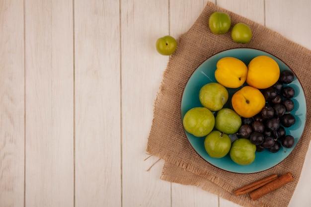 コピースペースを持つ白い木製の背景に袋の布の上の青い皿に緑のチェリーplumssloespeachesなどの新鮮な果物のトップビュー