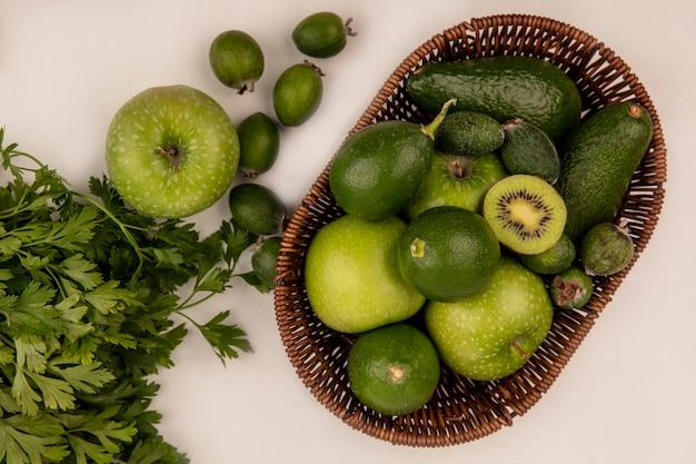 Вид сверху свежих фруктов, таких как киви, яблоки, авокадо, лаймы и фейхоа, на ведре на белой стене