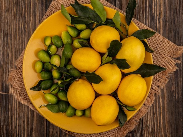 나무 표면에 자루 천에 노란색 접시에 레몬과 킨칸과 같은 신선한 과일의 상위 뷰