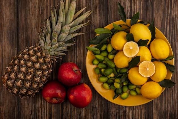 Вид сверху свежих фруктов, таких как лимоны и кинканы, на желтом блюде с ананасом и красными яблоками, изолированными на деревянной поверхности