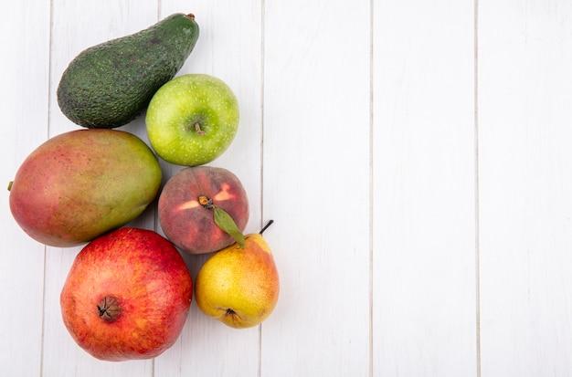 Вид сверху на свежие фрукты, такие как манго, груша, яблоко, гранат на белом с копией пространства
