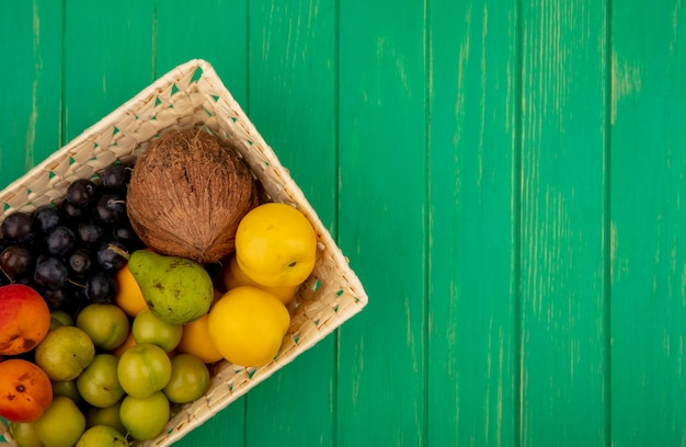 Вид сверху свежих фруктов, таких как персики, кокос, зеленая алыча, на ведре на зеленом фоне с копией пространства