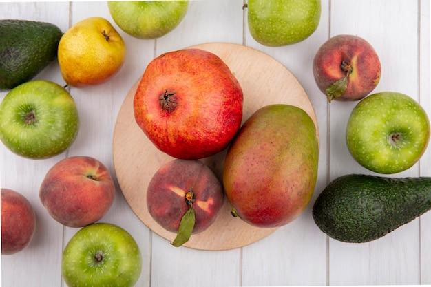 Вид сверху на свежие фрукты, такие как гранат, персик, манго на кухонной доске с зелеными яблоками, авокадо, персиковыми грушами, изолированными на белом