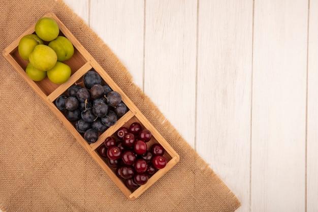 スローチェリーやグリーンチェリープラムなどの新鮮な果物の平面図、コピースペースを持つ白い木製の背景に袋布の木製分割トレイ
