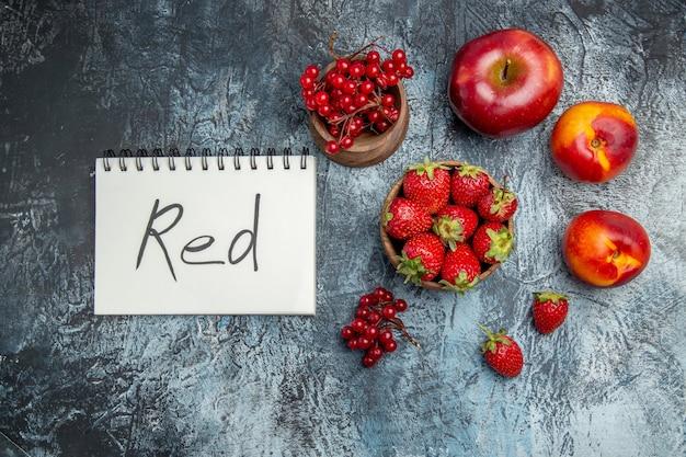 어두운 표면에 빨간색 서면 메모장으로 신선한 과일의 상위 뷰