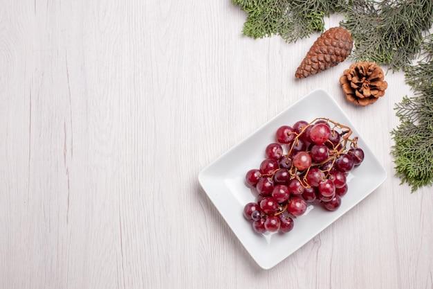 白いテーブルの上のプレート内の新鮮なブドウの上面図