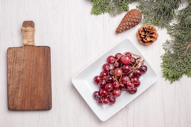 木製のテーブルの上に木とプレート内の新鮮なブドウの上面図