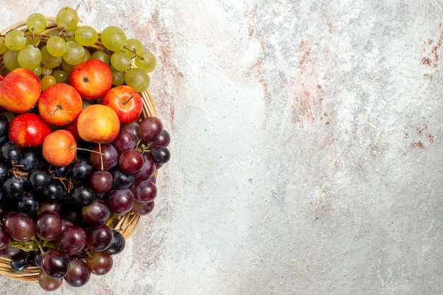 Вид сверху свежего винограда со сливами на белой поверхности