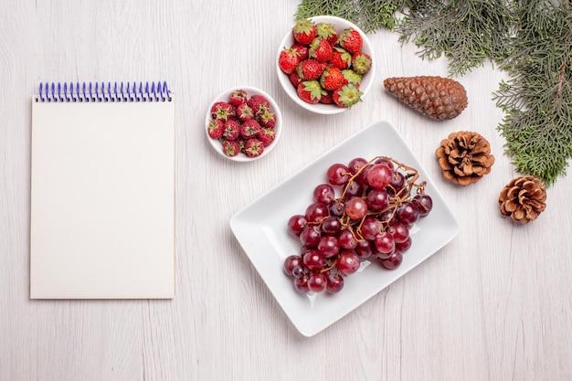白いテーブルの上のイチゴとラズベリーと新鮮なブドウの上面図