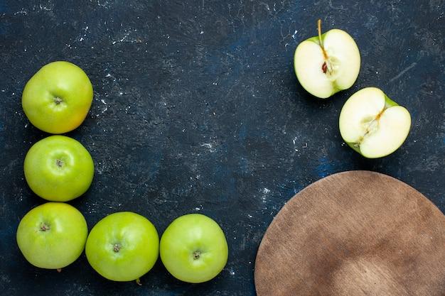 新鮮な青リンゴの組成の上面図、半分カットされたスライスされたものが暗い、果物の新鮮なまろやかな熟した上に並んでいます