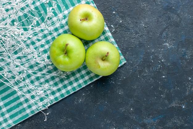 青く暗い机の上の新鮮な青リンゴのまろやかでジューシーな酸味の上面図、フルーツベリー健康ビタミン
