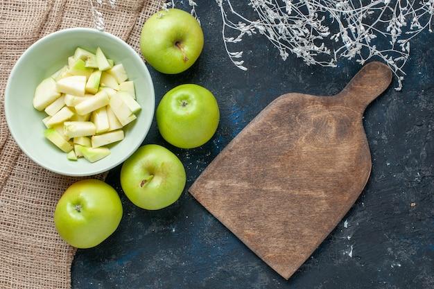 新鮮な青リンゴの上面図はまろやかでジューシーで、暗い机の上のプレートの内側にスライスされたリンゴ、フルーツの新鮮な健康ビタミン