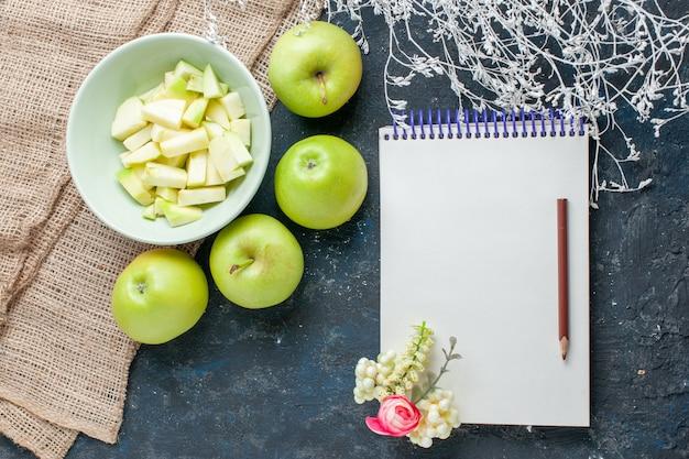 暗い床の果物の生鮮食品の健康ビタミンのプレートの内側のスライスされたリンゴとまろやかでジューシーな新鮮な青リンゴの上面図