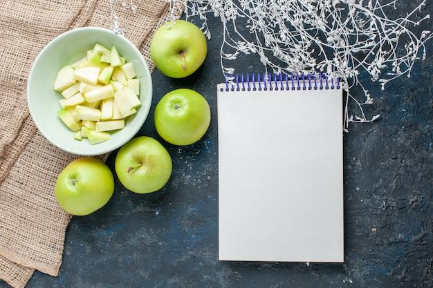 新鮮な青リンゴの上面図まろやかでジューシーで、スライスしたリンゴがプレートの内側にあり、暗いフルーツの新鮮な健康ビタミン