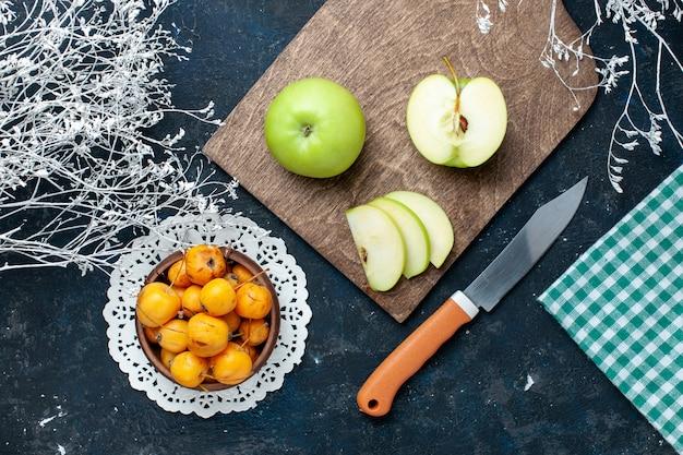 青く暗い机の上に甘いまろやかなサクランボ、フルーツの新鮮なまろやかな食品ビタミンと新鮮な青リンゴの上面図