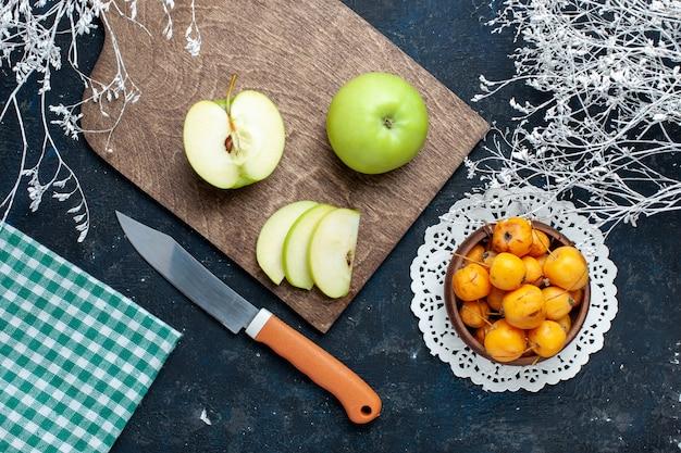 紺色の机の上に甘いまろやかなサクランボ、新鮮なまろやかな食品ビタミンと新鮮な青リンゴの上面図