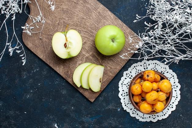 紺色の机の上に甘いまろやかなサクランボ、フルーツの新鮮なまろやかな食品ビタミンと新鮮な青リンゴの上面図