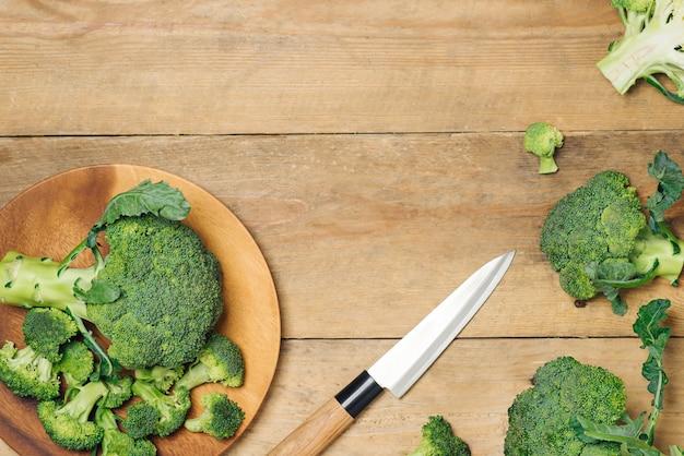 素朴な木製の背景に新鮮な緑のブロッコリーの上面図-健康またはベジタリアン料理。