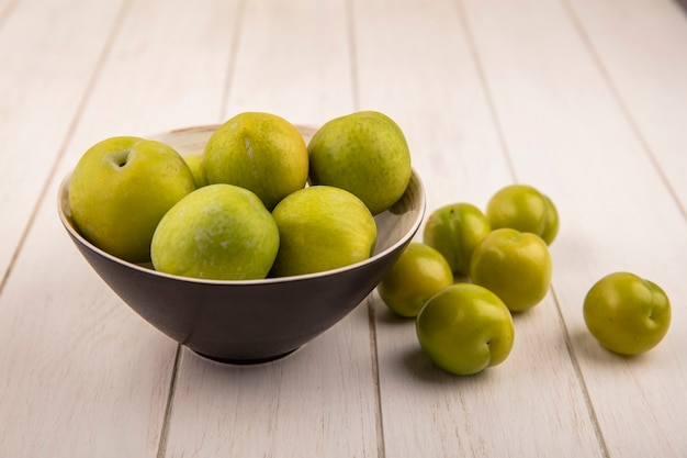 녹색 체리 자두 나무 배경에 고립 된 검은 그릇에 신선한 녹색 체리 자두의 상위 뷰