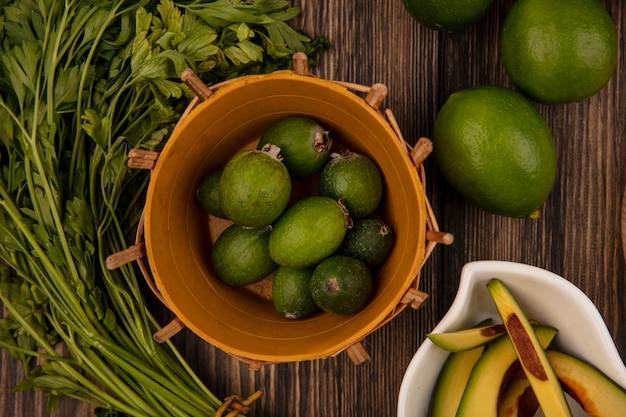 라임과 파 슬 리 나무 배경에 고립 된 그릇에 아보카도 슬라이스 양동이에 신선한 녹색 feijoas의 상위 뷰