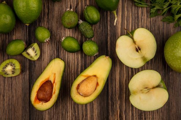木製の背景に分離されたフェイジョアアボカドリンゴやライムなどの新鮮な緑の食べ物の上面図