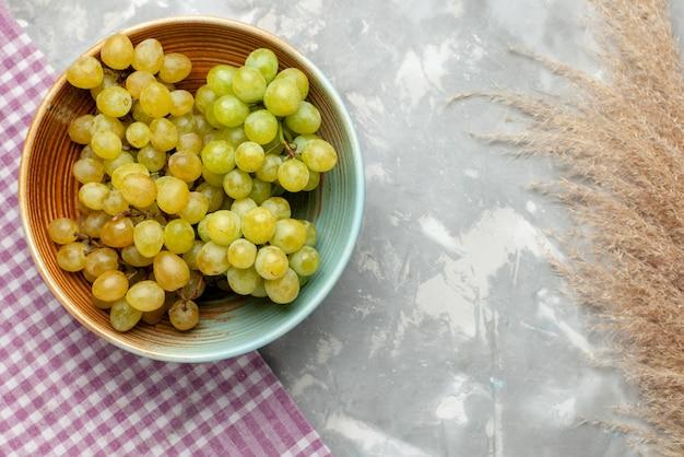 灰色の光、フルーツジューシーなまろやかなプレート内の新鮮な緑のブドウの果実の上面図