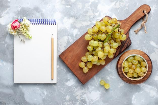 新鮮な緑のブドウの上面図は、軽くてフルーツのまろやかなジュースのメモ帳と一緒にジューシーでまろやかです