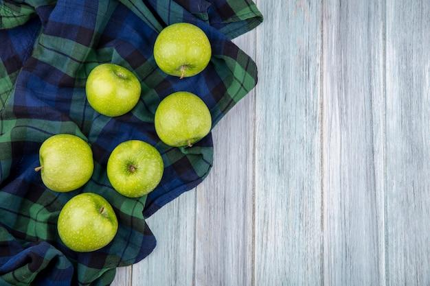 灰色の木の緑のチェックのテーブルクロスに新鮮な緑のジューシーなりんごの平面図