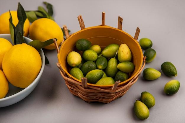 白い背景で隔離のキンカンとボウルにレモンとバケツの上の新鮮な緑のキンカンの上面図