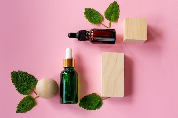 ピンクの背景に新鮮な緑のミントまたはスペアミントの葉とミントエッセンシャルオイルのガラススポイトボトルの上面図。天然ハーブ医療芳香植物のコンセプト。