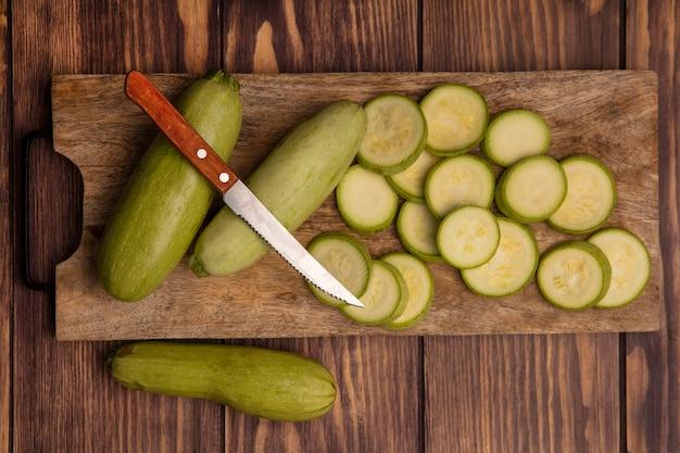 Вид сверху свежих зеленых цукини на деревянной кухонной доске с ножом с цукини, изолированными на деревянном фоне