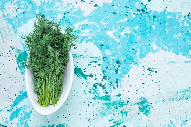 明るい青色の机、緑の葉製品食品食事野菜のプレート内に分離された新鮮な緑の上面図
